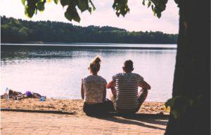 夫婦が湖の前で座っている画像